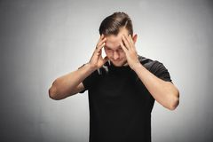 Confused and troubled young man. Young man grabbing his head, looking both troubled and confused. Studio portrait stock photography