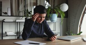 Confused unhappy indian businesswoman frustrated about phone problem in office