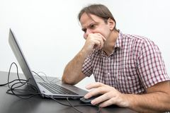 The confused unhappy user is looking at the computer Stock Image