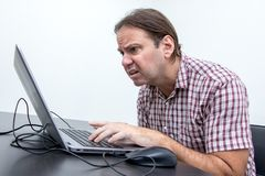 The confused unhappy user is looking at the computer. Screen. Surprised stressed man looking at laptop. System error on computer stock photography
