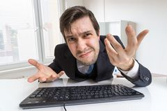 Confused and unsure man is working with computer.  stock images