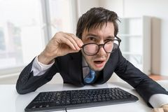 Confused or unsure man is working with computer and looking at you Royalty Free Stock Image