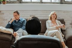 Confused and upset adult couple sitting on different sides of couch. Talking about life. Confused and upset adult couple sitting on different sides of couch and royalty free stock photography
