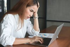 Confused upset young Asian business woman suffering from severe from depression in workplace. stock photos