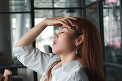 Confused upset young Asian business woman suffering from severe from depression in workplace royalty free stock photos