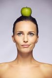 Confused woman with apple on her head Royalty Free Stock Images