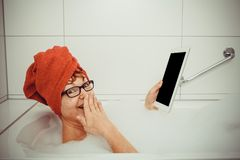 Confused woman in bathtub with tablet computers. Close up, retro style stock photos