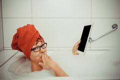 Confused woman in bathtub with tablet computers. Retro style stock image