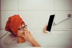 Confused woman in bathtub with tablet computers, space for text Stock Images