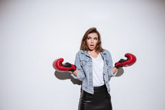 Confused woman boxer over white background. Image of confused woman boxer dressed in jeans jacket and gloves standing  over white background Royalty Free Stock Image