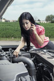 Confused woman with broken car Royalty Free Stock Image