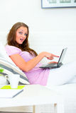 Confused woman couch pointing finger at laptop Royalty Free Stock Photos