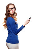 Confused woman in glasses. Hold smartphone in her hand and looking back royalty free stock photography