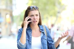 Confused woman having a phone conversation. Confused woman having a negative mobile phone conversation in the street Stock Photography
