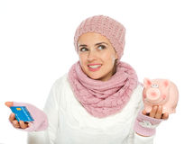 Confused woman holding credit card and piggy bank Stock Photos