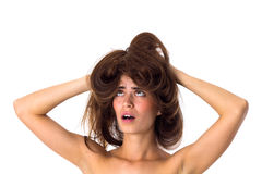 Confused woman holding her tangled hair. Young confused woman holding her long brown tangled hair on white background in studio Royalty Free Stock Image