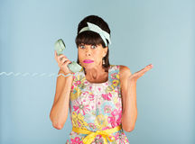 Confused woman holding telephone Royalty Free Stock Photography