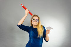 Confused woman holds big pencil note paper in hand Stock Images