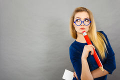 Confused woman holds big pencil note paper in hand. Woman confused thinking seeks a solution. Thoughtful student girl or business coach female teacher coming up stock images