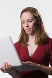 Confused woman with laptop-02. A young woman looks down at her laptop computer screen with a disconcerted look on her face Stock Photo