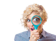 Confused woman. Woman looking at the camera through a magnifying glass with a surprised expression, isolated on white background Royalty Free Stock Photos