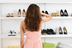 Confused Woman Looking At Shoes Displayed On Shelves Stock Photo
