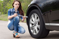 Confused woman looking at a wheel spanner. With a puzzled expression as she kneels in the road alongside her car which has broken down Stock Photos
