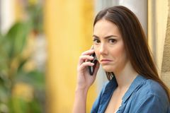 Confused woman looks at you talking on phone in the street royalty free stock photography
