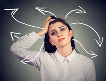Confused woman with many twisted arrows coming out of her head. Confused young woman with many twisted arrows coming out of her head Royalty Free Stock Images