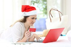 Confused woman paying online on christmas holidays. Lying on a bed in an hotel room royalty free stock images