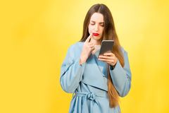 Confused woman with phone. Portrait of confused woman with mobile phone on the yellow background Stock Photos