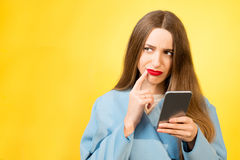 Confused woman with phone Royalty Free Stock Image