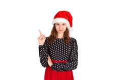 Confused woman pointing finger up. emotional girl in santa claus christmas hat isolated on white background. holiday concept stock images