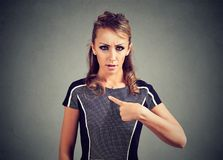 Confused woman pointing at herself with finger. Offended female having quarrel looking with wonder proving her guiltlessness Royalty Free Stock Photos