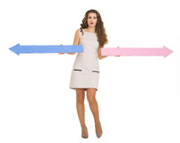 Confused woman pointing in opposite ways with arrows Royalty Free Stock Photography
