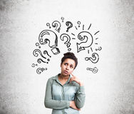 Confused woman with questions. Confused african american woman trying to find answers to her questions with question mark sketches on concrete background Stock Images