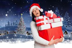 Confused woman in santa hat holding stack of christmas gifts Stock Photo