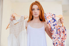 Confused woman standing and choosing clothes to wear Stock Image