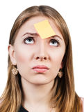 Confused woman with a sticker on her forehead Royalty Free Stock Images