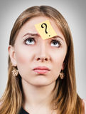 Confused woman with a sticker on her forehead. Over gray background Royalty Free Stock Photo