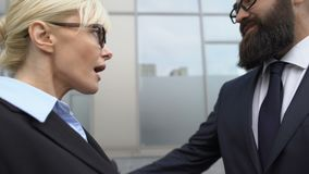 Confused woman stops male colleagues flirt attempt at work, workplace harassment