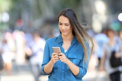 Confused woman checking phone on the street. Confused woman walking and checking smart phone on the street Stock Image