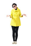 Confused woman in yellow coat wearing sunglasses shrugging shoulders. Full body length portrait isolated over gray studio background Stock Photos