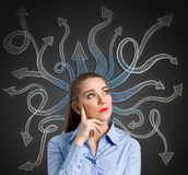 Confused woman. Confused, young businesswoman with many arrows pointed in different directions stock image