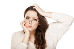 Confused woman. Confused young woman with eyeglasses scratching her head stock photography