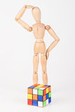 Confused wood mannequin stand next to puzzle confused before att. Empt to solve it Royalty Free Stock Images