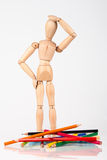 Confused wood mannequin standing at heap of colour pencil isolat Royalty Free Stock Images
