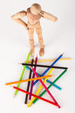 Confused wood mannequin standing at pencils Royalty Free Stock Photography