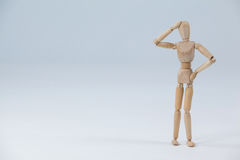 Confused wooden figurine standing with hand on head Stock Photos