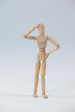 Confused wooden figurine standing with hand on head Stock Photography